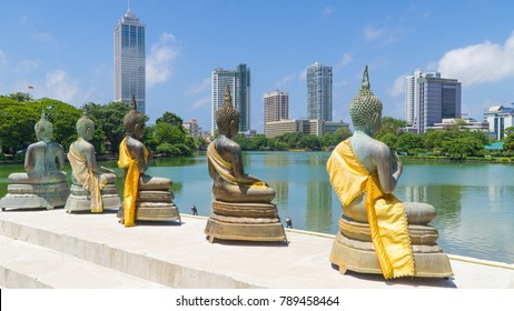 Line of Buddhas outside a Sri Lankan temple in Colombo, with the Colombo city skyline in the background.