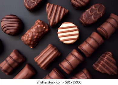 Line of chocolates of different shapes on a black background. all the candy black and milk chocolate, one white round candy.