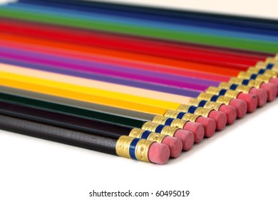 Line of colored pencils at an angle, on white