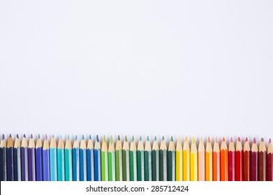 line of colored pencils on white background