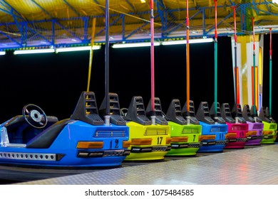 A line of colorful, electric bumper cars in autodrom in the fairground attractions at an amusement park.