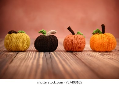 Line of colorful hand knit pumpkins