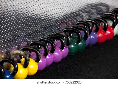 Line up of colorful kettlebell weights at a gym