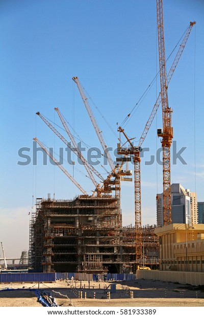 A line of cranes on a construction site.