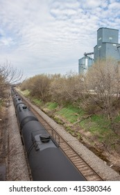A line of crude oil tank cars pass a grain elevator under a summer sky