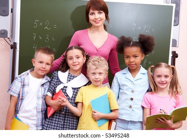 Line of cute schoolchildren looking at camera with their teacher near by