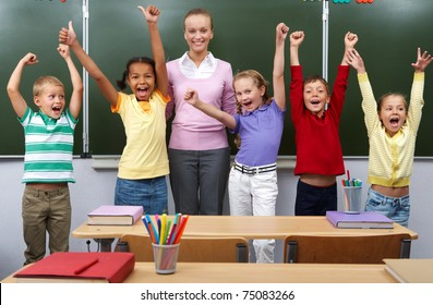 Line of cute schoolchildren raising arms with their teacher in the middle