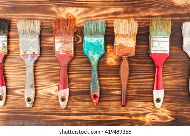 Line from different colorful brushes on the wooden background