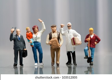 Line of diverse tiny miniature model people in population demographics representing a cross section of the community including a housewife, artisan, labourer, and professionals
