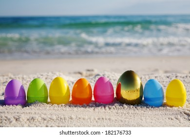 Line of easter eggs with gold egg on ocean beach