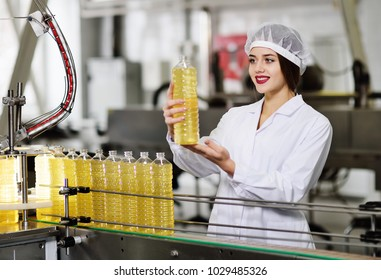 line of food production of refined sunflower oil. Girl worker at a factory on a conveyor background with bottles of vegetable oil.