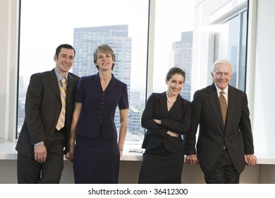 Line of four businesspeople smiling and standing at an office window with city view in background.