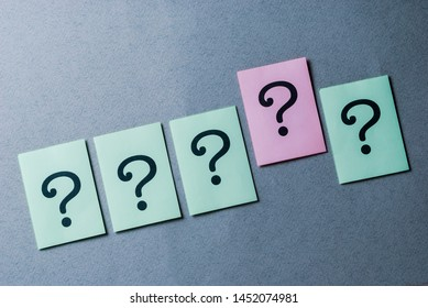 Line of four printed question marks on green paper and one on pink over a grey background
