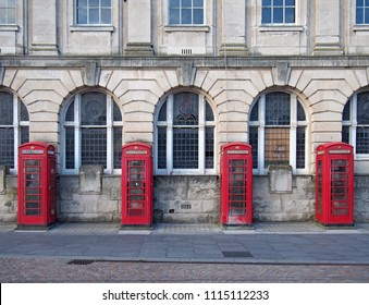 a line of four traditional british red phone boxes outside an old post office building in blackpool england
