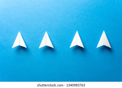 Line of four white paper airplanes concept, leadership, teamwork, motivation concept on blue background