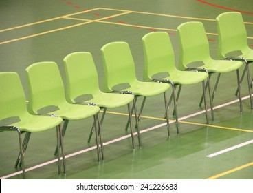 Line of green chairs in sports hall