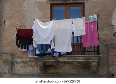 line of hanging clothes in front of balcony in corleone sicily