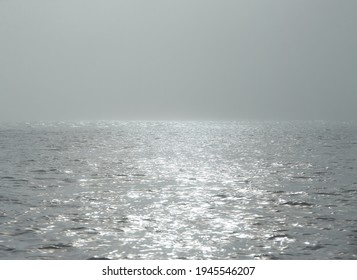 The line of the horizon, dissolving in the fog. Foggy weather with detail of a sunlight reflecting in glittering sea. sparkling in water - background. sea water with sun glare and ripple.