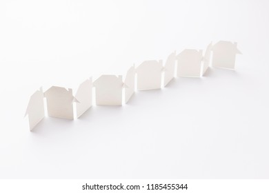 line linked of paper cutout houses on white background, selective focused point, shallow depth of field.