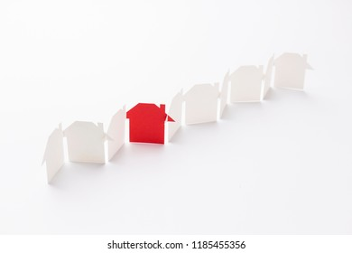 line linked of paper cutout houses with red one on white background, selective focused point, shallow depth of field.