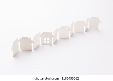 line linked of paper cutout houses with detail one on white background, selective focused point, shallow depth of field.