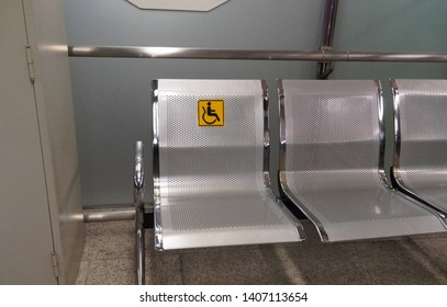 A line of lobby chairs with the one specially notified by a yellow sign attached to the backrest is understandable to be a priority seat for the handicapped at a waiting area in the train station.