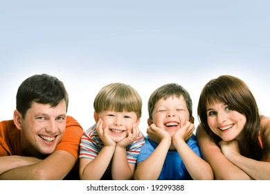 Line of mother, father and their two sons looking at camera with happy smiles
