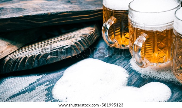 Line of mugs with light beer or ale on rustic wood. Closeup wide view