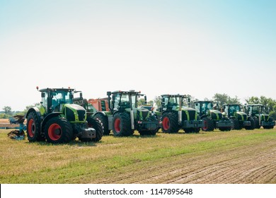 Line of new trucks presented in the field under the sky. Outdoor agricultural machinery fair.