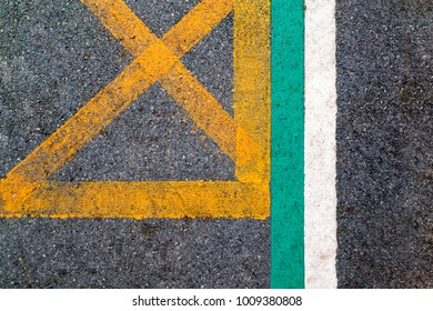 Line of old asphalt road texture with yellow and green and white cross