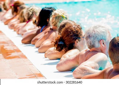 line of people doing exwercise in a pool taken from the back