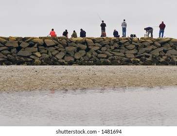 A line of people fishing from the breakwater in the Saco River in Biddeford Pool Maine.