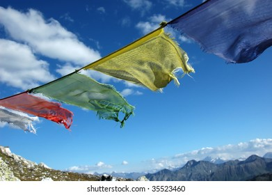 a line of prayer flags fluttering in the wind on a mountain pass which is on a pilgrimage route