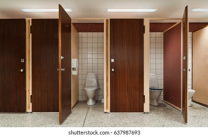 Line of public toilets some with open and some with closed door