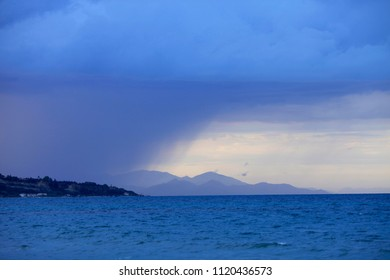 A line of rain between the sea and the sky off the coast of the island of Zakynthos in Greece