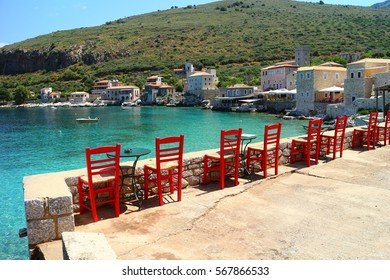 A line of red chairs overlooking the blue sea and the stone houses in Limeni, Mani, Peloponnese