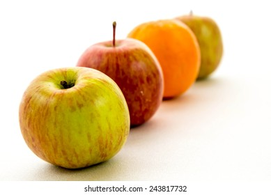 line of red and green apples with one orange