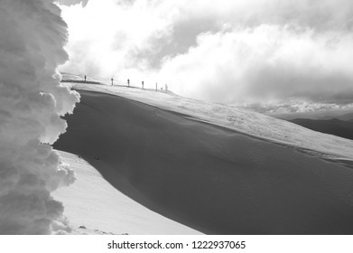 A line of road signs is dwarfed by a snow-covered mountain. Deep shadows run down the slopes. An ice-covered sign frames the shot. The photograph is in black and white. Storm clouds fill the sky.