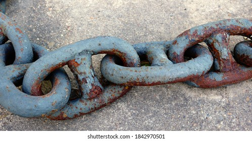 line of rusty heavy links of a thick anchor chain, on the ground - closeup of an industrial object in the harbor