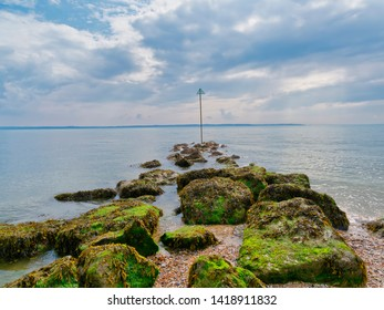 A line of seaweed covered rocks lead out in to the the estuary on Lee on Solent beach.