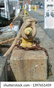 Line securing commercial fishing boat to horn cleat on wharf