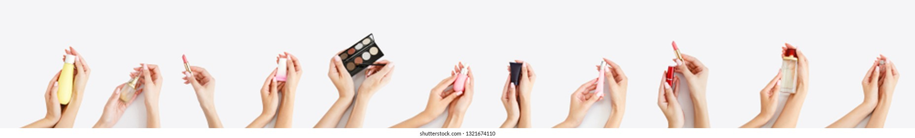 Line from several female hands with makeup products in them. Copy space. Daily care of beauty. Face care product. Banner of woman`s cosmetics on white background. Girl`s morning skin care. Make up