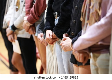 A line of standing young people with hands snesitively clasped showing or paying repsect. Possible silent protest, prayer, respect or remberance concept.