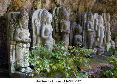 Line of stone statues at Mitaki Dera a temple in a forested valley near Hiroshima, Japan
