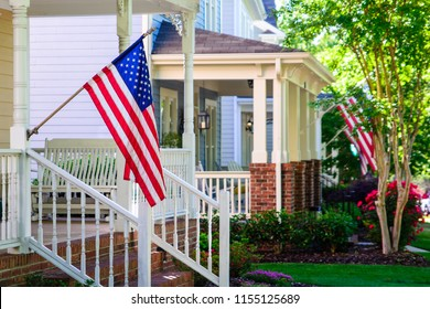 A line of suburban homes display large American Flags