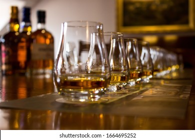 A line of tasting glasses filled with different types of Whiskies for tasting, with the focus on the second glass, the rest is out of focus