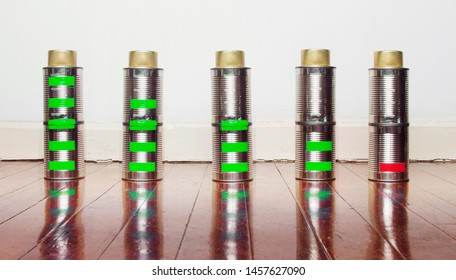 a line of tin can battarys from fully charged to emty on a old wooden floor