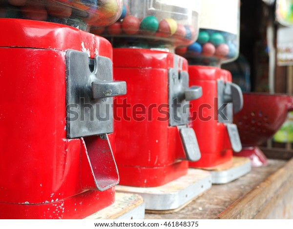 Line of vintage gumball machine on wooden table