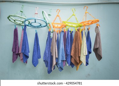 Line of washed towels hanging on colorful plastic pegs in front of pale blue wall background - close up objects