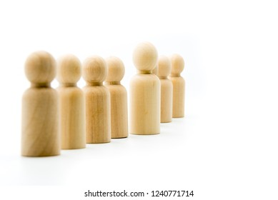 Line of wooden figures, standing out from the crowd and leadership concept. Selective focus on the figurine in front